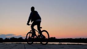 Een tiener op een twee-wiel zelf-in evenwicht brengt hoverboard en een kerel op een fietsrit voorbij elkaar dichtbij de vijver la stock footage