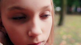 Een tiener raakt haar haar en denkt over iets stock videobeelden