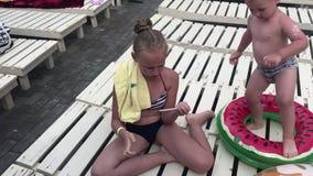 Een tiener speelt op een smartphone, zittend op een houten deckchair Een kleine jongen speelt rond stock video