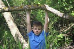 Een tiener stelt voor een fotograaf terwijl het lopen in het park Hangen, die de boom zoals een dwarsbalk clutching stock fotografie
