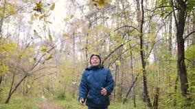 Een tiener werpt boven op gele bladeren Een gang in het pijnboombos stock footage