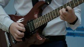 Een tiener in een wit overhemd speelt een bruine elektrische gitaar De kerel trekt koorden met een bemiddelaar en klemt zijn lijs stock footage