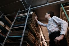 Een tiener in een wit overhemd trekt een boek van het rek in een van het boekopslagruimte of archief ruimte terug Het bestuderen  stock foto's