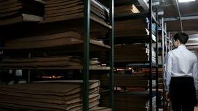 Een tiener in een wit overhemd zoekt een kleine jongen tussen de planken met oude boeken Donkere ruimte in de bibliotheek of stock video