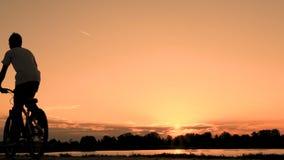 Een tiener in een witte T-shirt op een fiets berijdt voorbij een rivier of een meer vroeg in de ochtend bij dageraad Silhouet van stock videobeelden