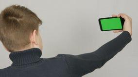 Een tienerjongen bevindt zich met van hem terug naar de camera en houdt ter beschikking een zwarte smartphone met het groen scher stock video