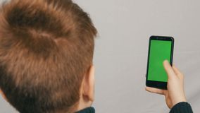 Een tienerjongen bevindt zich met van hem terug naar de camera en houdt ter beschikking een zwarte smartphone met het groen scher stock videobeelden