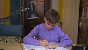 Een tienerjongen doet thuiswerk afstandsonderwijs Onderwijs thuis stock videobeelden