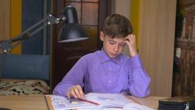 Een tienerjongen doet thuiswerk afstandsonderwijs Onderwijs thuis stock video