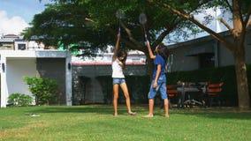 Een een tienerjongen en meisje spelen badminton op een groen gazon in de binnenplaats van hun huis stock video