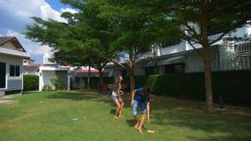 Een een tienerjongen en meisje spelen badminton op een groen gazon in de binnenplaats van hun huis stock videobeelden