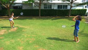 Een een tienerjongen en meisje spelen badminton op een groen gazon in de binnenplaats van hun huis stock footage