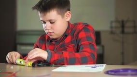 Een tienerjongen in een plaidoverhemd snijdt een stuk van ABS plastiek voor een 3D pen af stock footage
