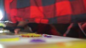 Een tienerjongen snijdt bovenmatig plastiek met schaar af Hij creeert een 3D cijfer van plastiek stock videobeelden