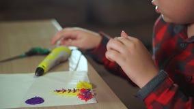 Een tienerjongen snijdt bovenmatig plastiek met schaar af Hij creeert een 3D cijfer van plastiek stock footage