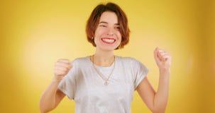 Een tienermeisje kruiste haar vingers en wacht een partij tegen een gele achtergrond Donkerbruin meisje dat op de resultaten word stock footage