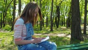 Een tienermeisje trekt op aard Een meisje in armbanden trekt in het park Handen van een tiener stock footage