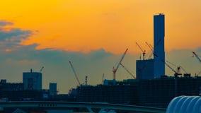 Een tijdtijdspanne van het bewegen van kranen in in aanbouw Tokyo bij schemer schoot binnen wijd panning stock video