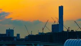 Een tijdtijdspanne van het bewegen van kranen in in aanbouw Tokyo bij schemer schoot binnen wijd panning stock videobeelden