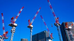 Een tijdtijdspanne van het bewegen van kranen in in aanbouw Tokyo schoot binnen wijd panning stock videobeelden