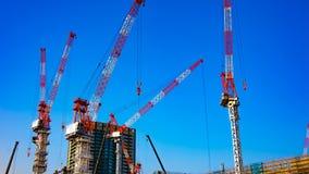 Een tijdtijdspanne van het bewegen van kranen in in aanbouw Tokyo schoot binnen wijd panning stock video