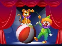 Een tijger en een clown die in het stadium presteren Stock Foto