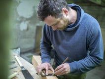 Een timmerman met een baard merkt het houten straalvierkant stock foto's