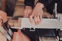 Een timmerman werkt bij de houtbewerking de werktuigmachine Timmerman die aan houtbewerkingsmachines werken in timmerwerkwinkel stock foto's