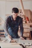 Een timmerman werkt bij de houtbewerking de werktuigmachine Timmerman die aan houtbewerkingsmachines werken in timmerwerkwinkel stock afbeeldingen