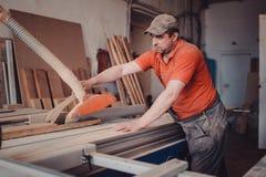 Een timmerman werkt bij de houtbewerking de werktuigmachine Timmerman die aan houtbewerkingsmachines werken in timmerwerkwinkel royalty-vrije stock afbeeldingen