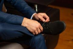 een toekomstige echtgenoot verscherpt voor een huwelijk door op zijn schoenen te zetten en zijn banden te binden royalty-vrije stock fotografie