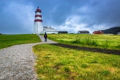 Een Toerist bezoekt Alnes-Vuurtoren bij Godoy-Eiland dichtbij Alesund stock foto