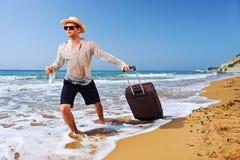 Een toerist die een koffer draagt bij het strand Stock Fotografie