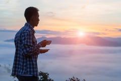 Een toerist die een kop van koffie op de berg houden, de vallei is stock afbeeldingen