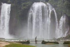 Een toerist die op een bamboebrug dichtbij een deel van de waterval van Verbodsgioc in Vietnam lopen Stock Fotografie