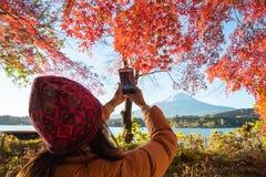 Een toerist doet fotografie Fujisan met esdoornbladeren royalty-vrije stock afbeeldingen