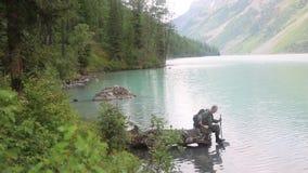 Een toerist kwam aan een gedronken te worden bergmeer stock footage