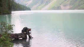 Een toerist kwam aan een gedronken te worden bergmeer stock videobeelden