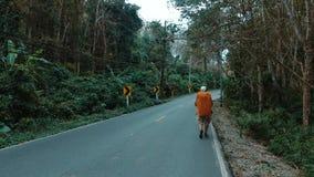 Een toerist loopt langs de weg stock video