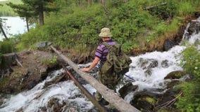 Een toerist loopt langs een logboek over de rivier stock footage