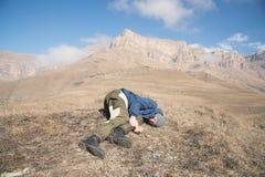 Een toerist met een hoed en een baard ligt op de grond en voelt slecht in de bergen Een persoon die bewustzijn heeft verloren stock afbeelding