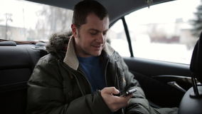 Een toerist op de rug van een taxi op de telefoon stock video