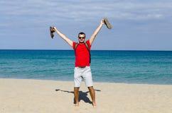 Een toerist op de strandgolven zijn handen met opwinding en vreugde Royalty-vrije Stock Foto's