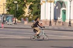 Een toerist op een het vouwen fietsritten door het stadsvierkant royalty-vrije stock foto