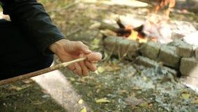 Een toerist zet een worst op een houten vleespen aan gebraden gerecht op een brand Gebraden gerechtworsten op stokken stock footage