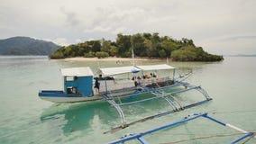 Een toeristenboot op de achtergrond van het eiland CYC-strand Coron PALAWAN filippijnen stock videobeelden