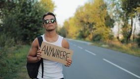 Een toeristenlifter loopt overal langs de weg met een rugzak op zijn schouder en teken De reiziger probeert op te houden stock footage