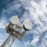 Een toren met satellietschotels en radioantennes tegen de blauwe hemel Stock Afbeeldingen