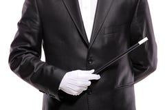 Een tovenaar in een kostuum dat een toverstokje houdt Royalty-vrije Stock Foto's