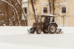 Een tractor met borstels verwijdert sneeuw op de piste Stock Afbeelding